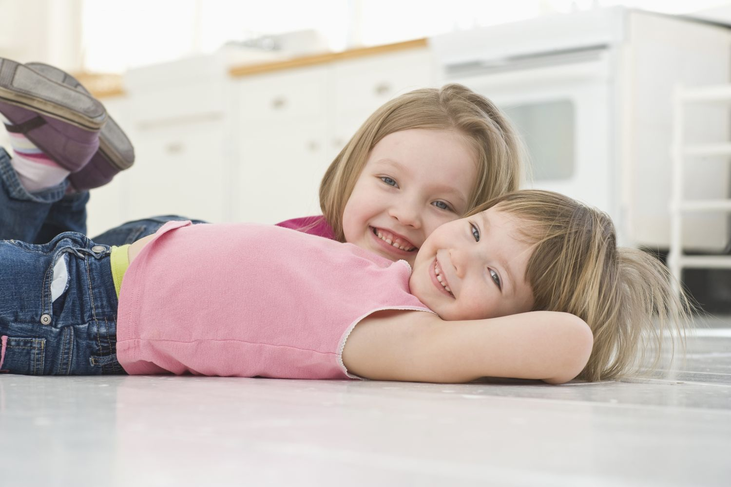 Little girls laying on clean kitchen floor after our complete pest control services in Trinity, NC