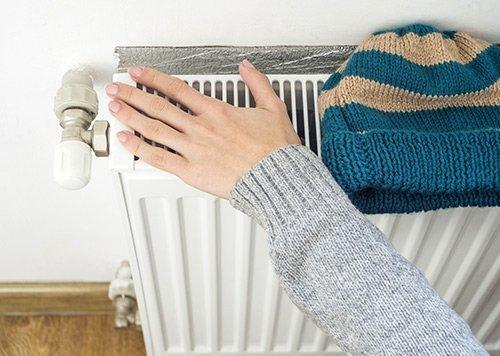 una mano femminile controlla il calore di un termosifone