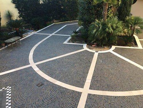 pavimento esterno in pietra con dettagli in bianco