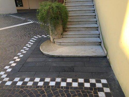 scala esterna in marmo con pavimento in pietra e bordo a scacchi