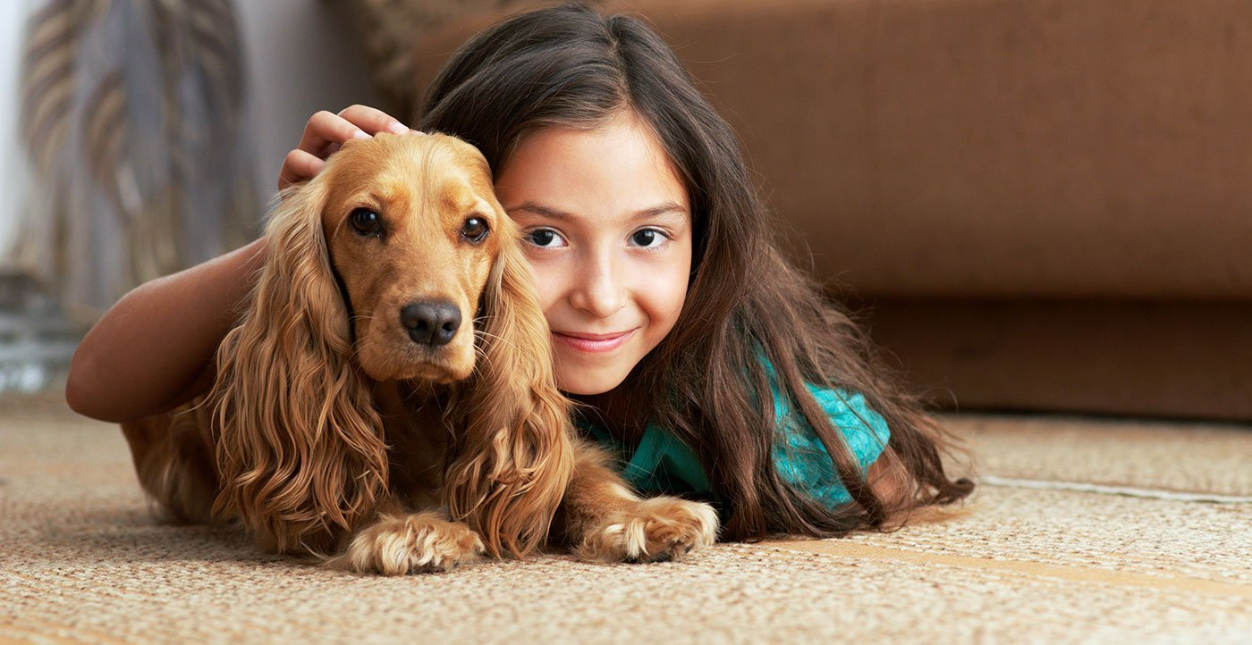 Young girl with her dog lying on quality carpet