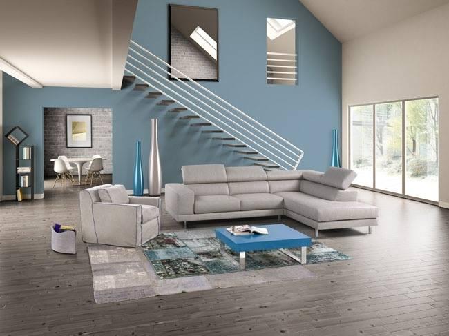 un divano  di color grigio e davanti un tavolino di color azzurro