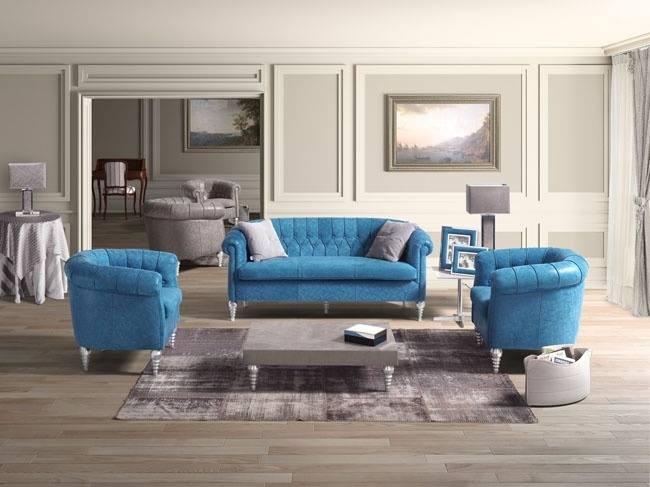 un divano con tre posti e due poltrone in pelle di color azzurro