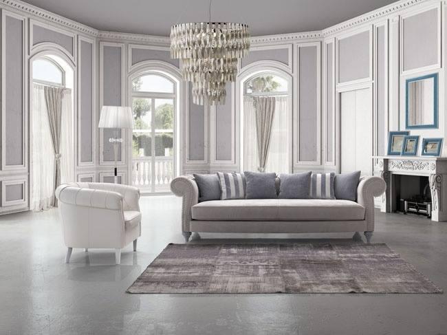 una sala con un divano e una poltrona e un lampadario a sospensione