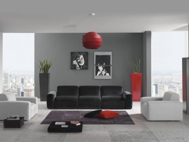 una sala con un divano di color nero e due poltrone di color bianco