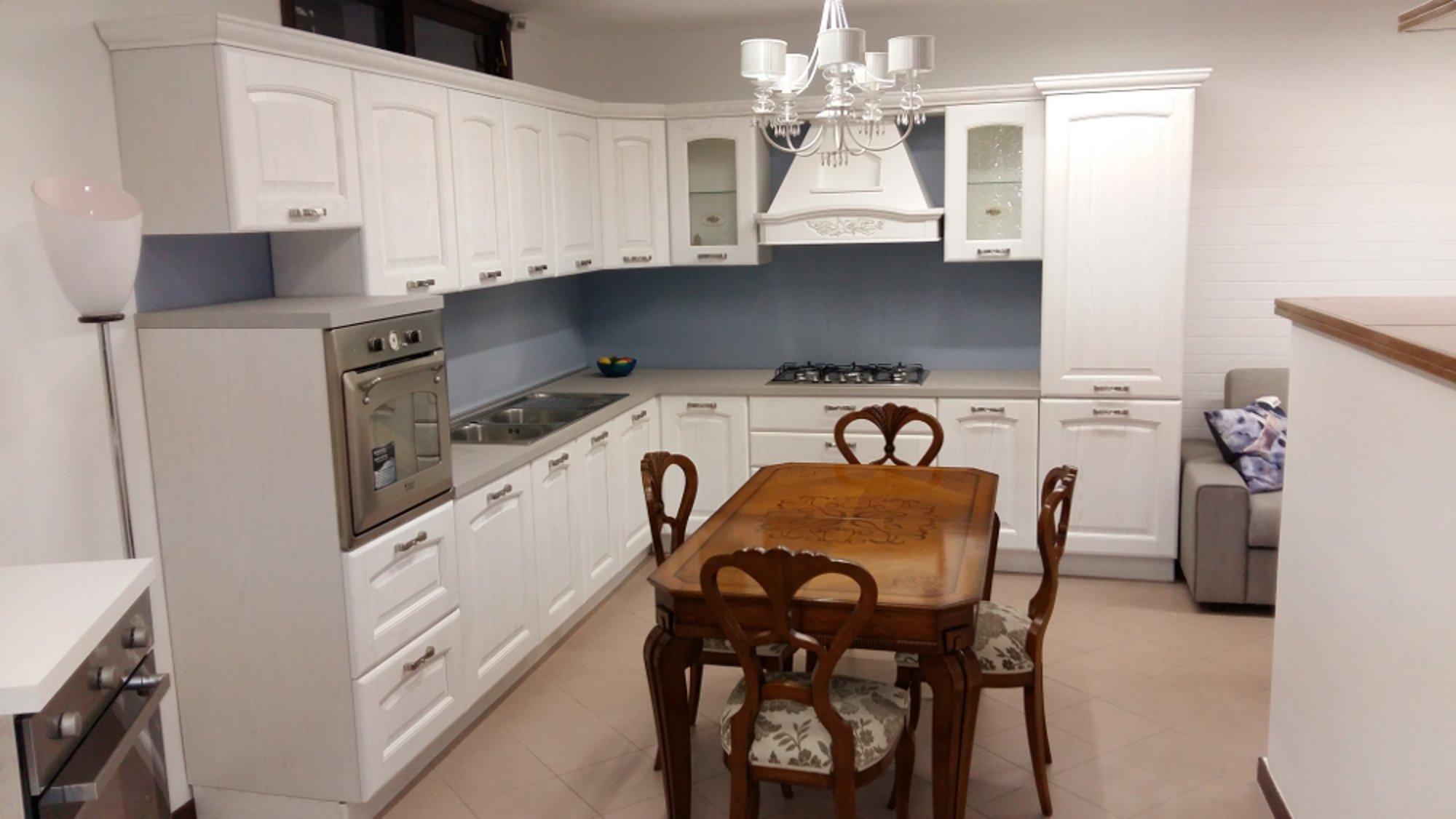 una cucina con mobili in legno di color bianco