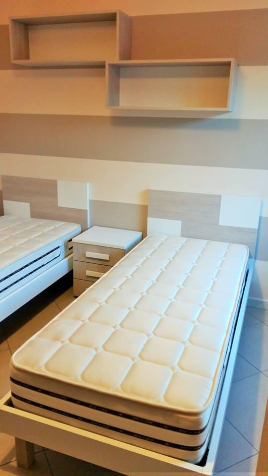 una cameretta con un letto singolo un armadio e una scrivania