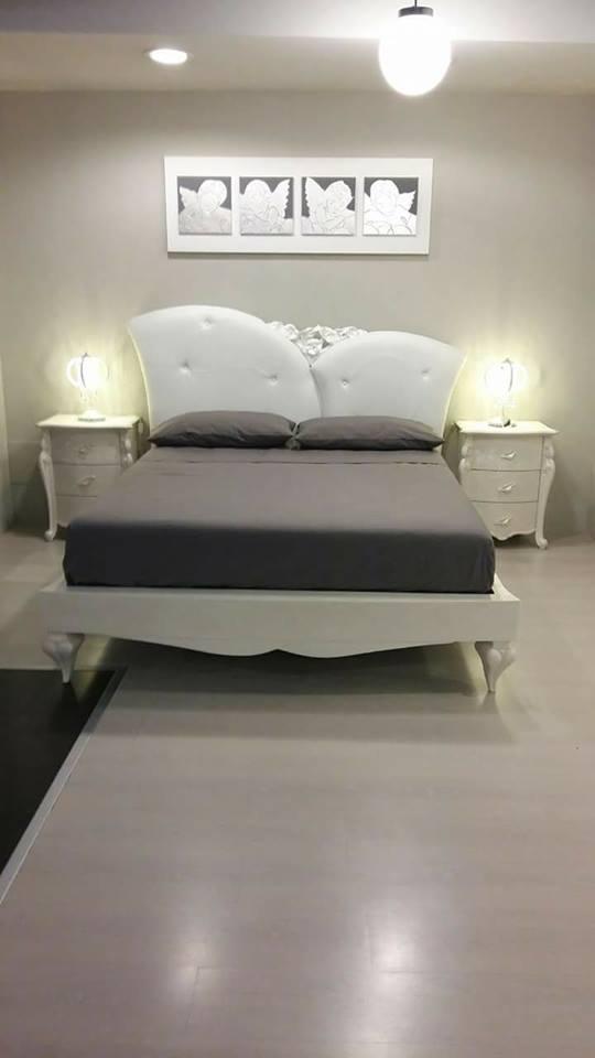 un letto e due comodini di color avorio