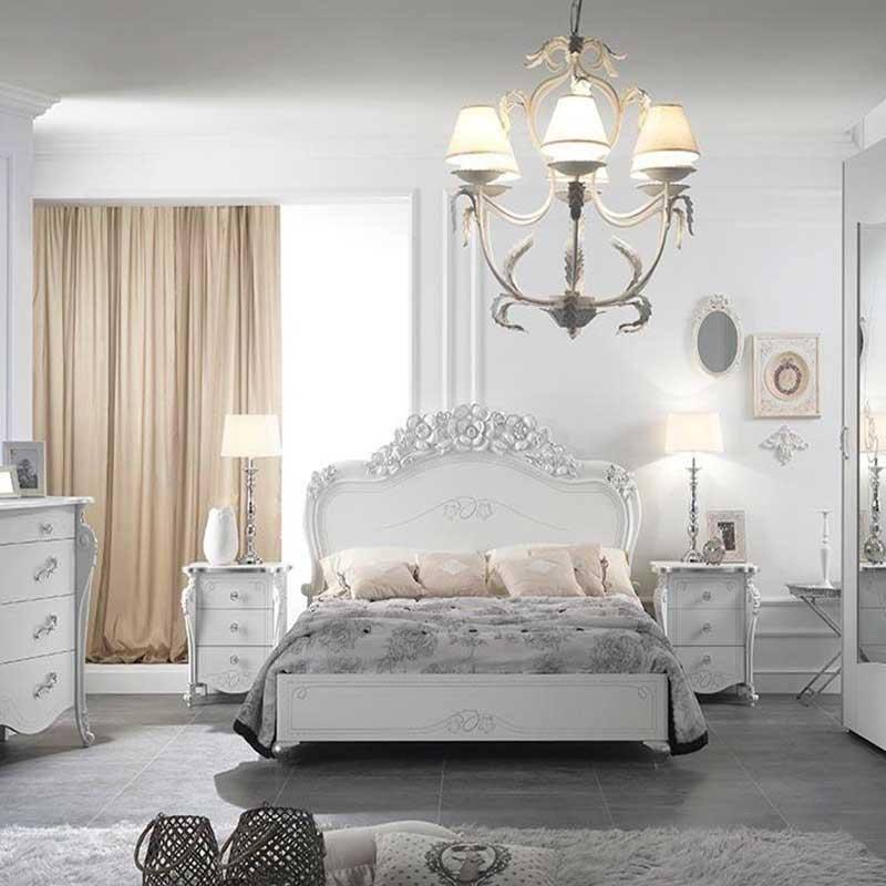 una camera con un letto, due comodini e un como di color bianco