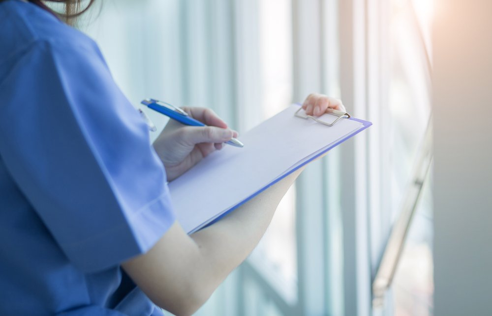 femmina medicina medico mano che tiene la penna che scrive una prescrizione sul un foglio