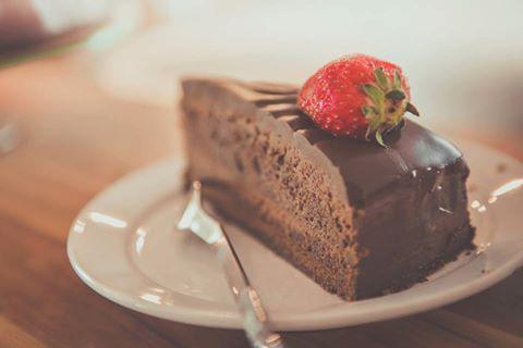 una fetta di torta al cioccolato con sopra una fragola
