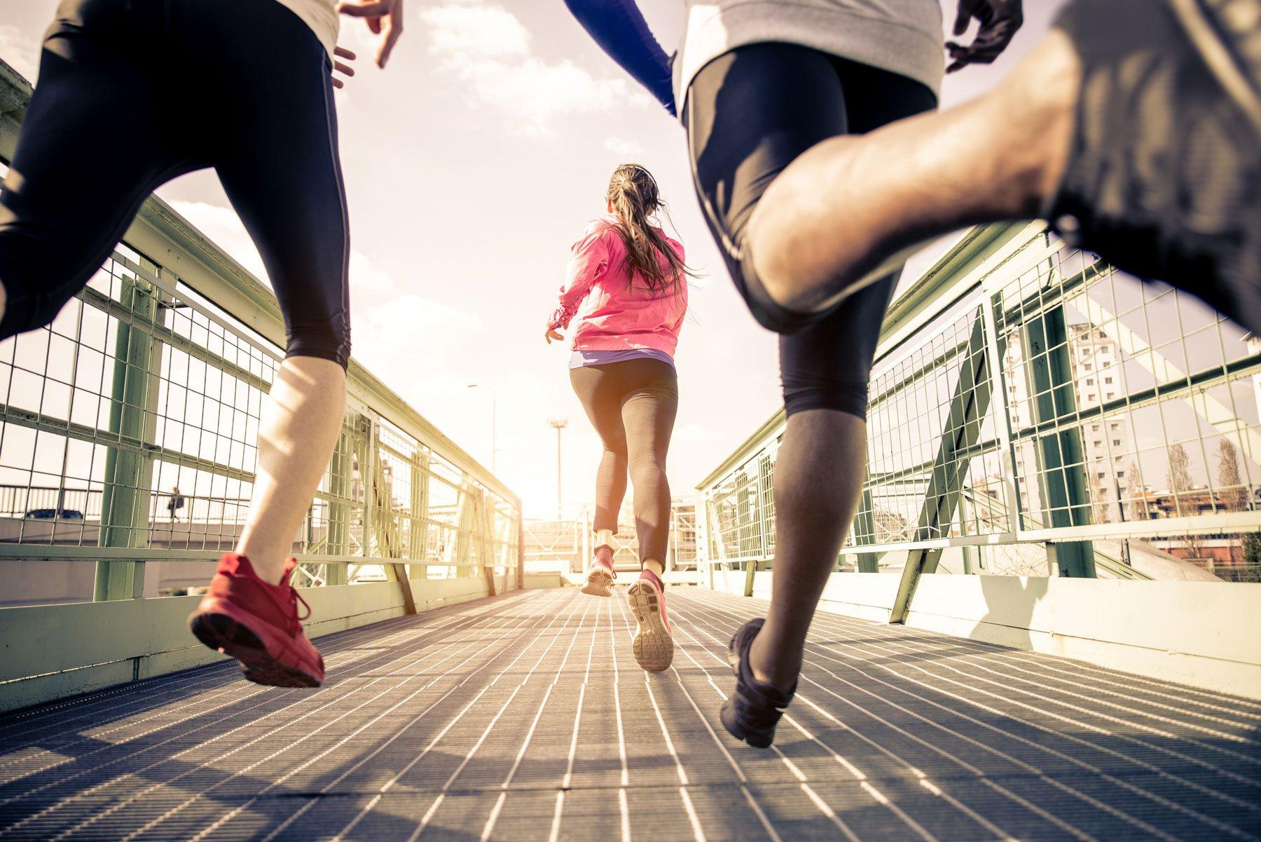 Tre corridori che sprintono all'aperto per uno stile di vita sano e concetti di sport