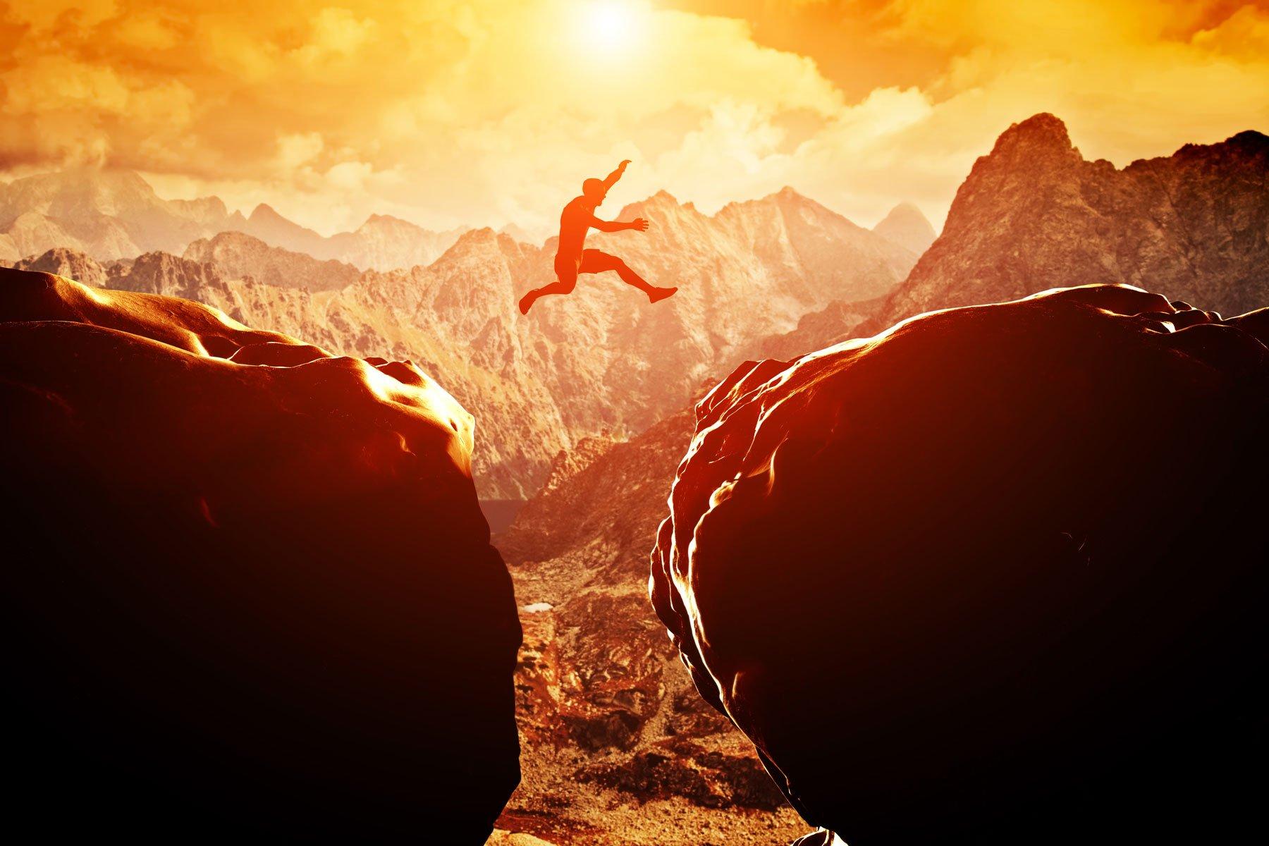 Uomo che salta sul precipizio tra due montagne rocciose al tramonto.