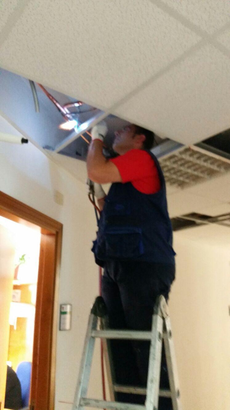 un uomo su una scala al lavoro con dei cavi su un soffitto