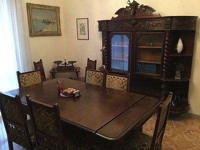 una stanza con un tavolo e dei mobili in legno visto da una diversa angolazione