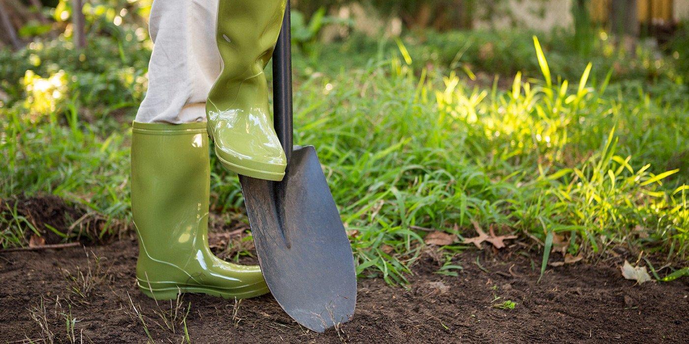 Vista dal basso di un giardiniere con stivali verdi,e una pala nel giardino