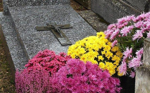 Tomba di granito con crocifisso, fiori rosa e gialle