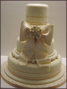 A large cream bow around a cream and peach three tier cake