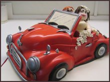 Bride and groom in red Morris Minor cake