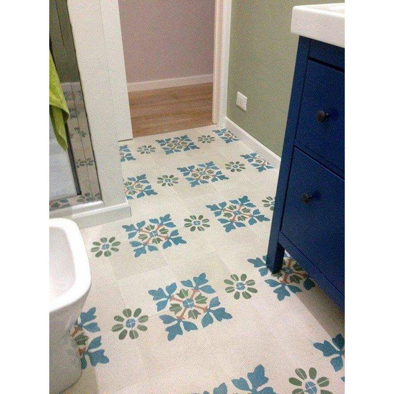 un bagno con delle piastrelle di color bianco e deii disegni ai fiori azzurri
