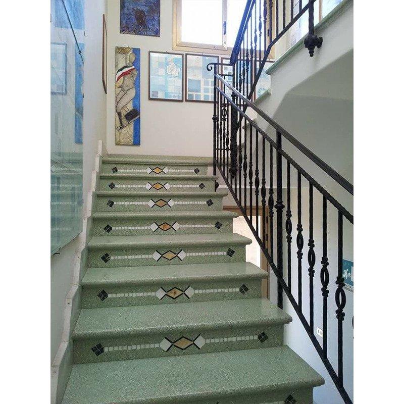 delle scale di color grigio con i corrimano in ferro battuto