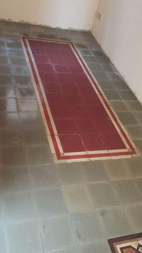 un pavimento con le piastrelle di color grigio e rosso al centro