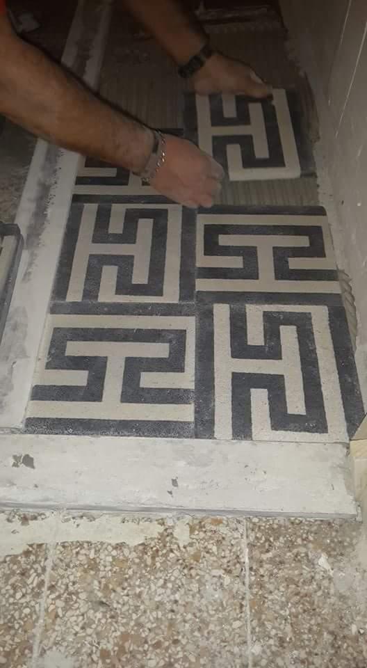 due mani mentre installano delle piastrelle di color nero e grigio