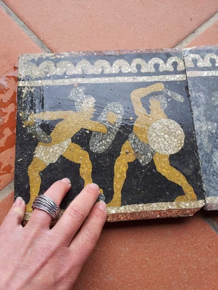 una mano appoggiato su una piastrelle di color nero con due guerriere