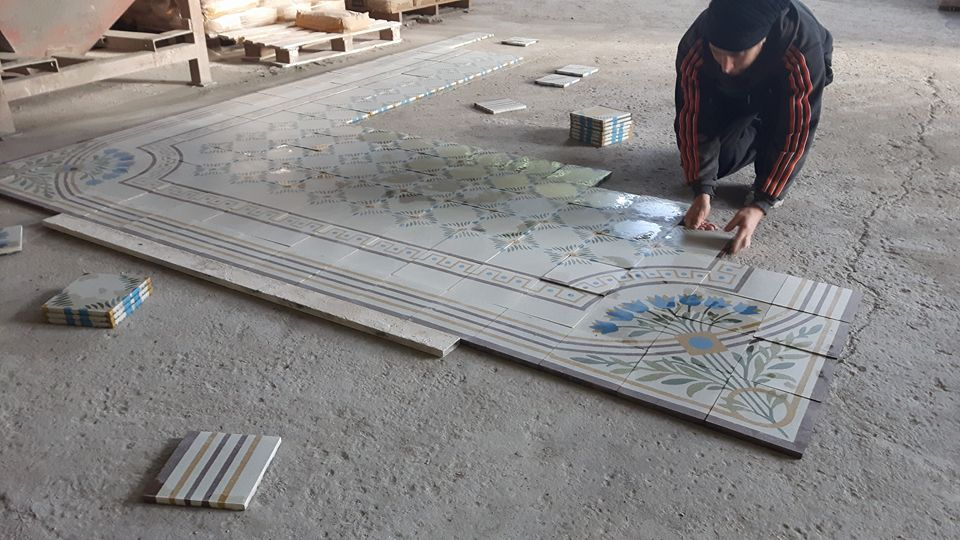 un uomo mentre appoggia le piastrelle sul pavimento in un magazzino