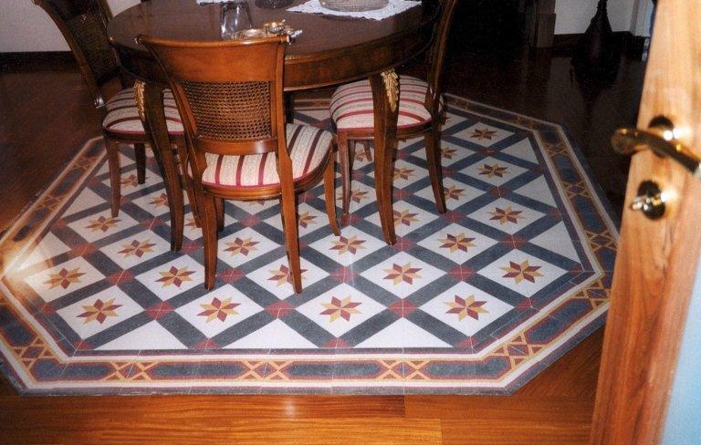 un tavolo in legno e un disegno a mosaico sul pavimento