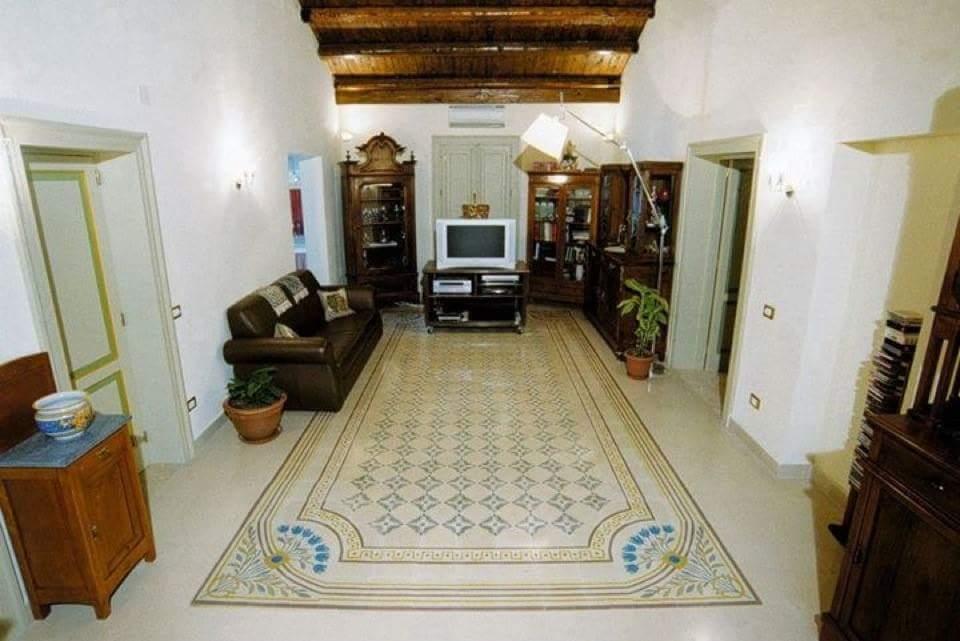 una sala con i mobili in legno e pavimento con i disegni di fiori di color azzurro