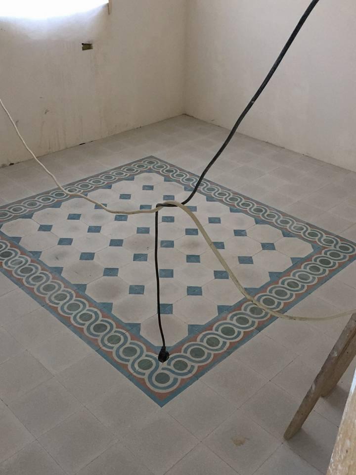 un pavimento con delle piastrelle di color grigio e dei disegni di color azzurro