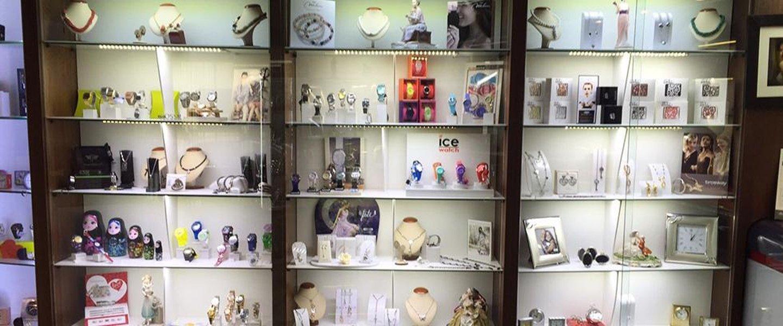 tre vetrine espositive con orologi, collane e matrioska