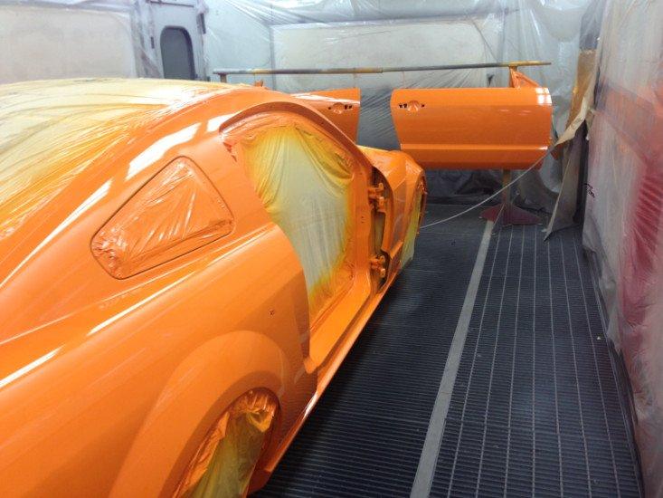 una macchina verniciata di arancione in un forno di una carrozzeria