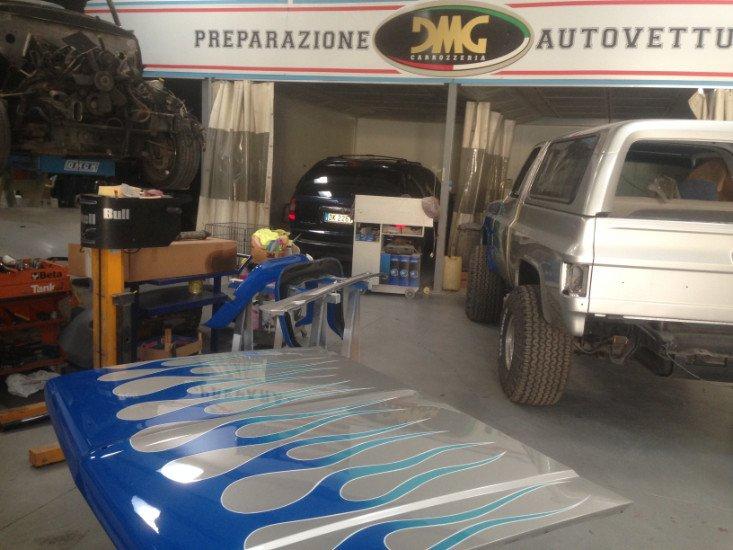 dei veicoli nella carrozzeria e un cofano color bianco verniciato a fiamme blu
