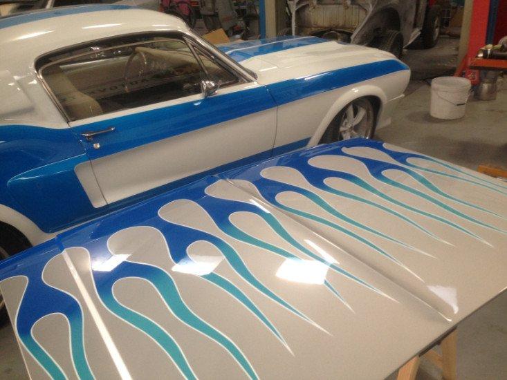 un cofano bianco a fiamme blu e accanto una macchina dello stesso colore
