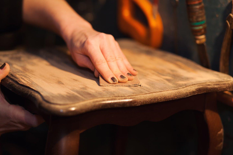 mano che scartavetra una sedia in legno