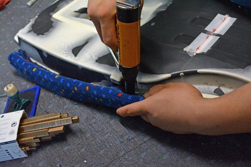 mani che assicurano con il trapano  il corretto incastro della tappezzeria al sedile