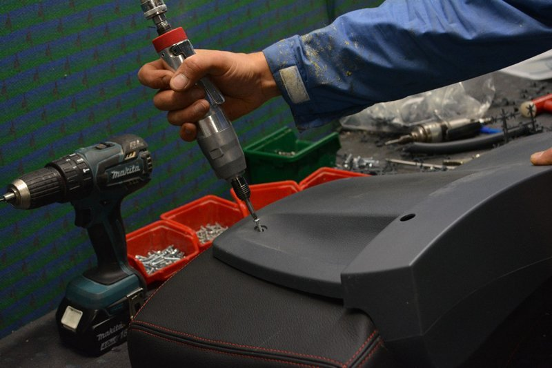 mano di un meccanico che assicura con un cacciavite un chiodo in un sedile auto