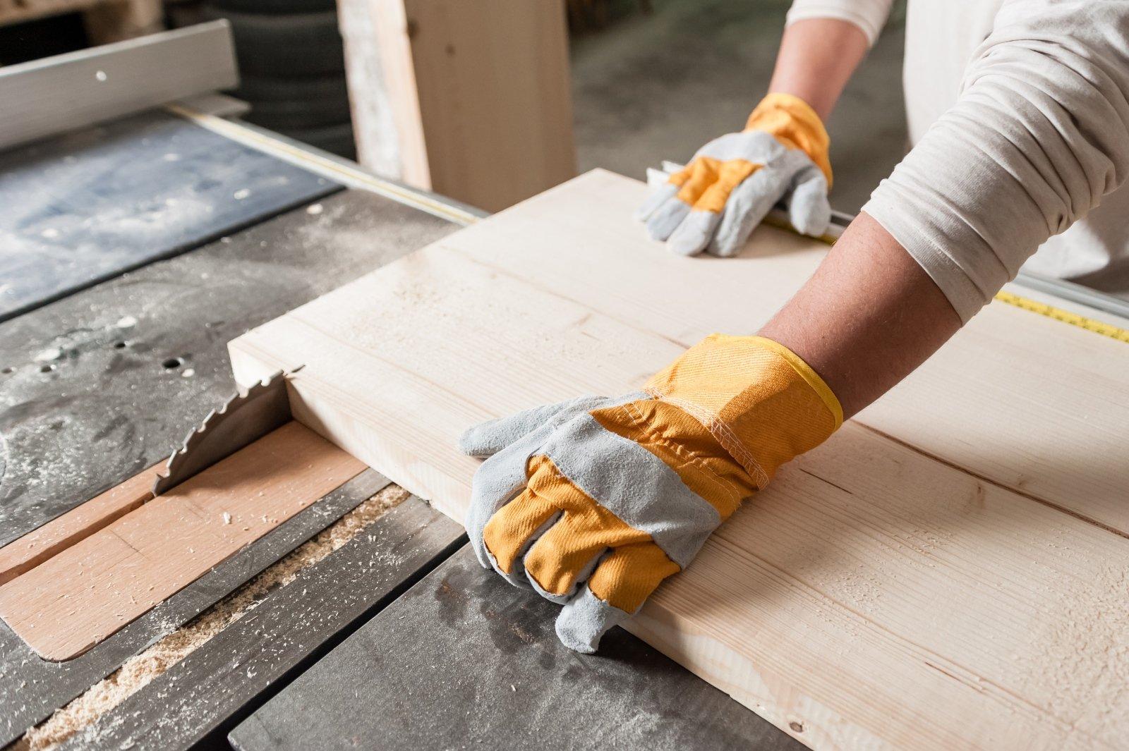 operaio che lavora legno con sega elettrica