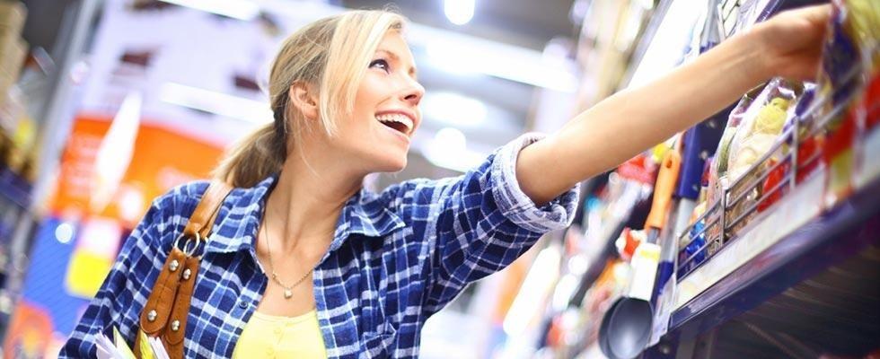 Donna felice prendendo un prodotto sullo scaffale