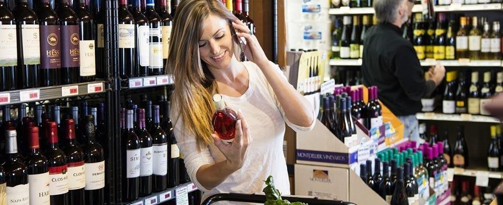 Donna con una bottiglia di vino nella mano parlando al cellulare