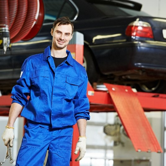 Smiling auto mechanic at work
