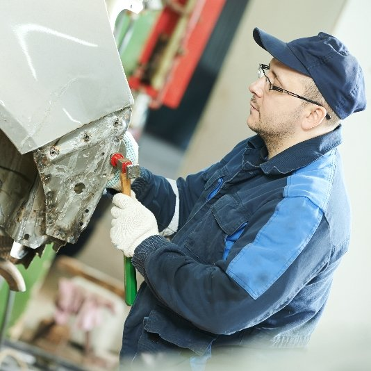 Auto mechanic performing straightening services