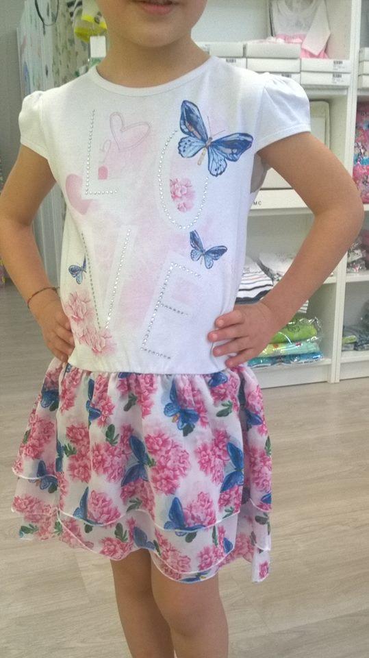 una bambina con una maglietta bianca a farfalle colorate e una gonnellina bianca a fiori blu e fucsia