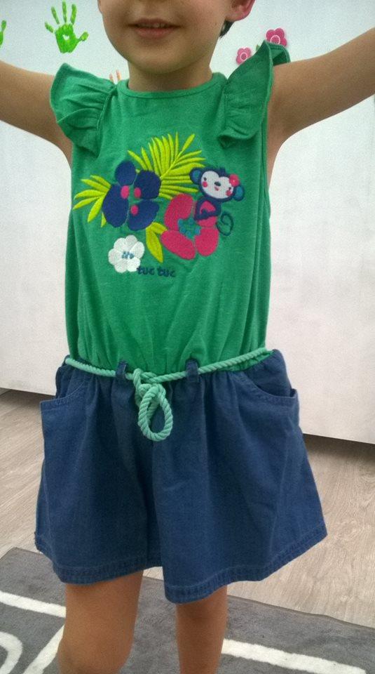 un bambino con una canotta verde a disegni e dei pantaloncini blu