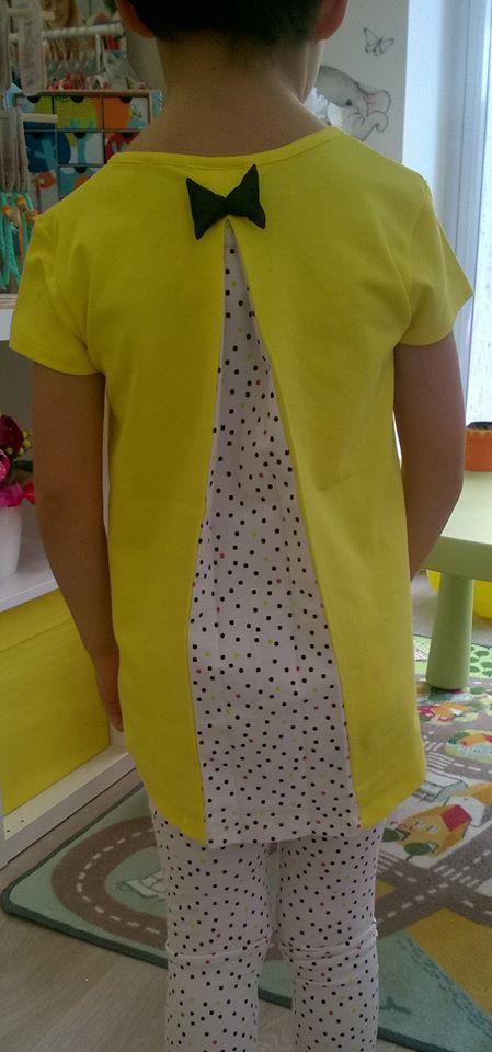 una bambina con una maglietta gialla e un papillon nero visto da dietro