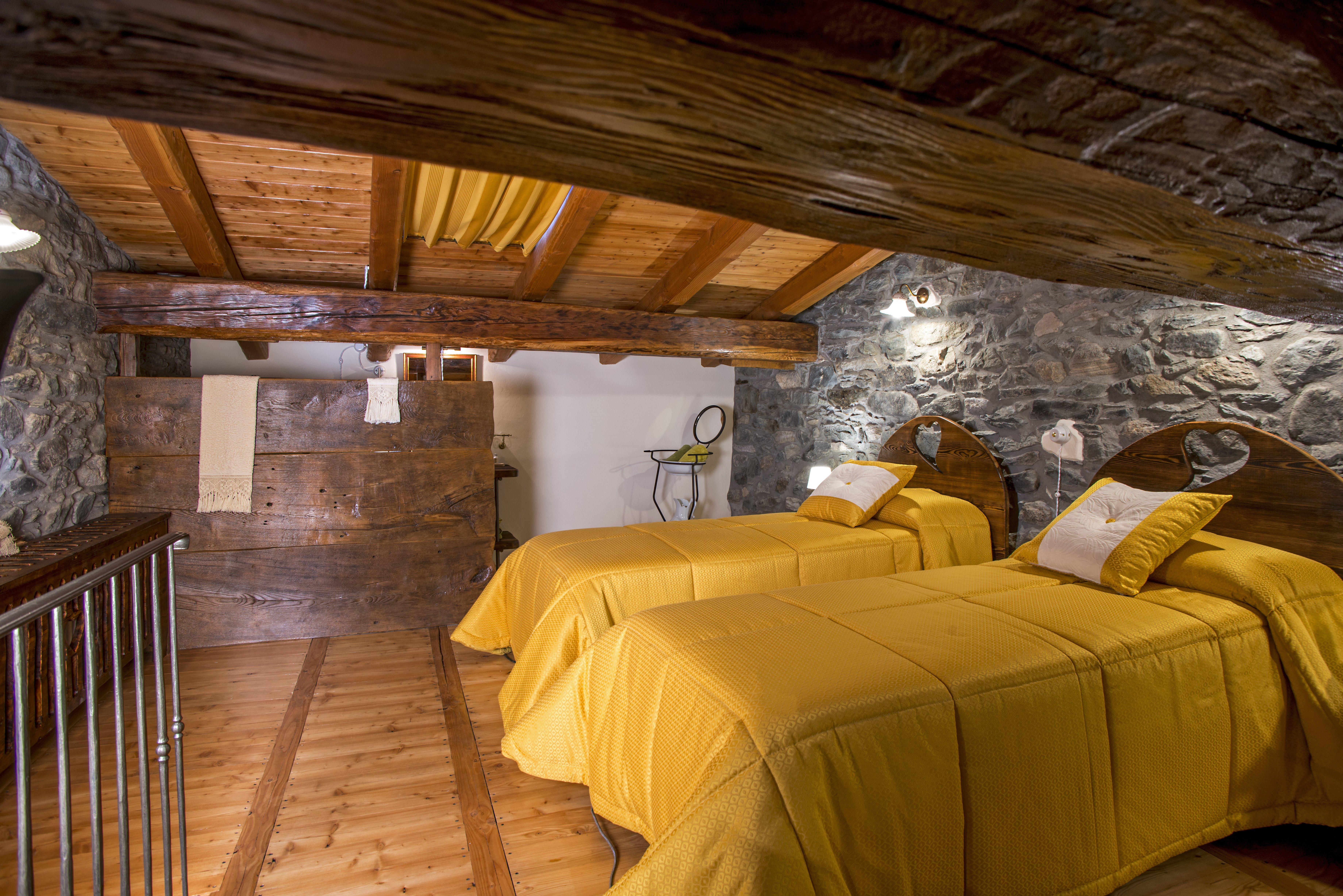camera da letto mansarda con copriletto giallo