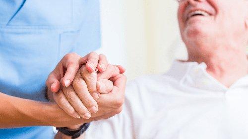 infermiera tiene la mano di una persona anziana