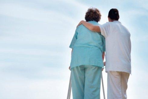 Infermiere e anziana abbracciati
